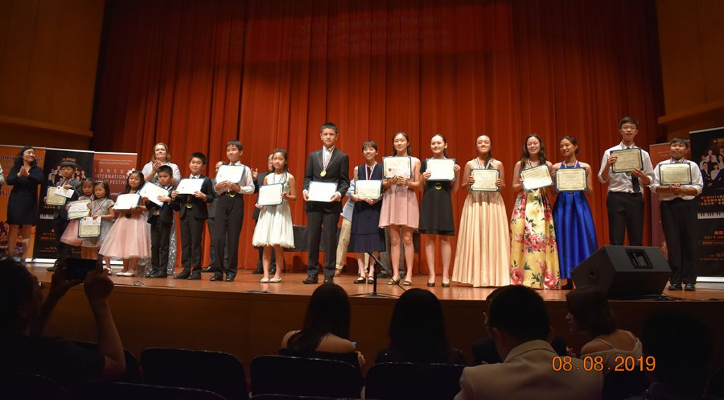 A group of Little Chopin competition winners standing on-stage during the 2019 LANSUM awards ceremony